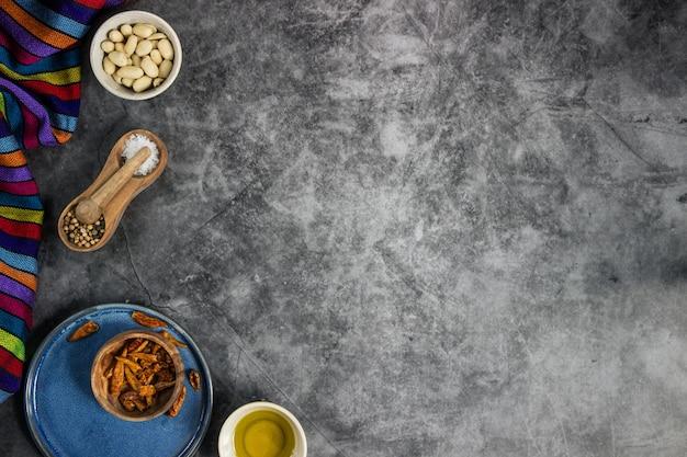 Piments rouges, arachides, sel, poivre et huile d'olive pour préparer un plat mexicain sur un tableau noir disposé sur le côté