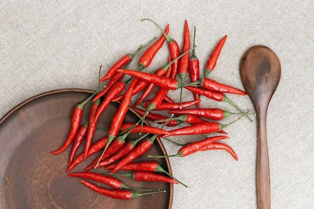 Piments rouges chauds dispersés d'une assiette sur la table.