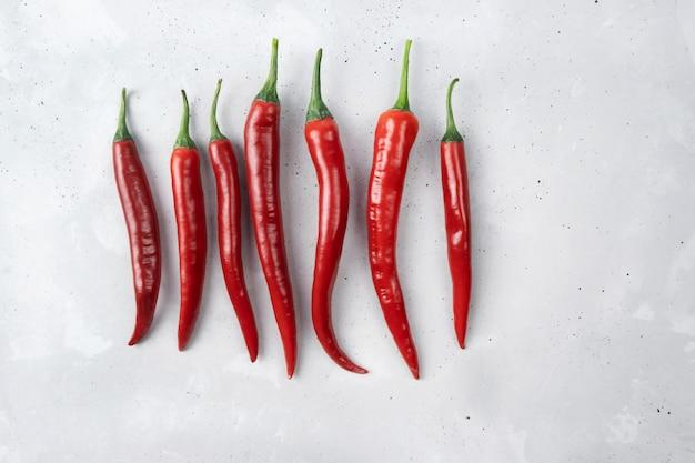 Piments rouges chauds frais disposés dans une rangée sur un fond de béton gris.