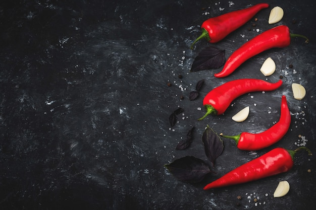Piments rouges chauds sur une surface noire,