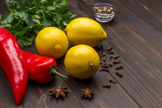 Piments rouges, épices verts de citron sur table. fermer. copiez l'espace. surface en bois foncé. vue de dessus
