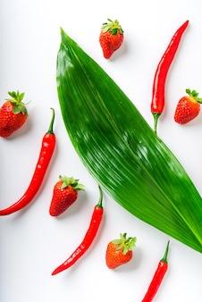 Piments rouges et fraises mûres et feuilles vertes sur fond blanc 1