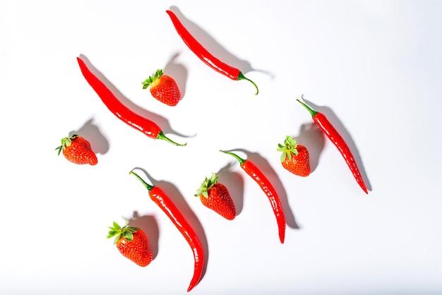 Piments rouges et fraises mûres sur fond blanc 1