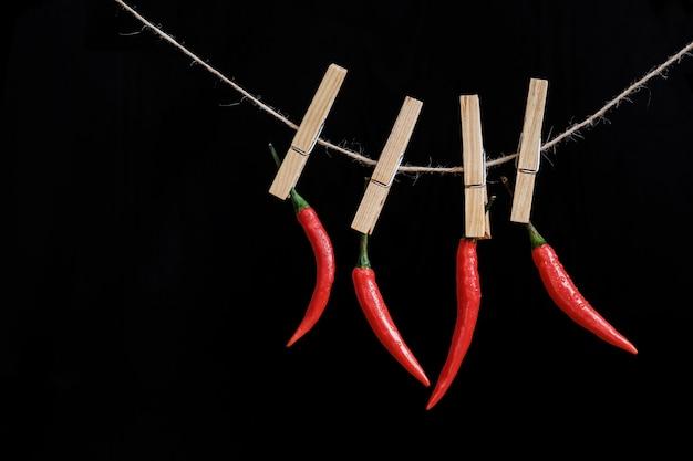 Piments rouges pendent sur une pince à linge sur une corde sur un fond noir. épice chaude. fermer.