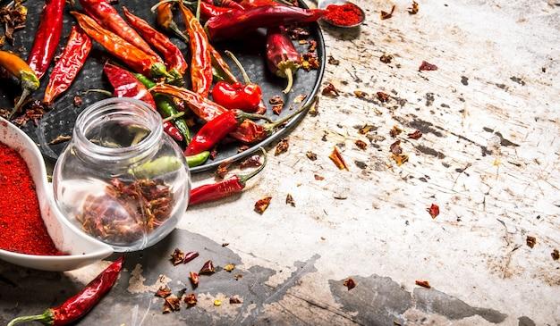 Piments rouges séchés sur plateau et en pot sur table rustique.
