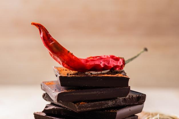 Piments rouges secs sur des barres de chocolat avec de la poudre de cayenne