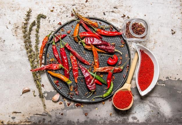 Piments séchés sur un plateau avec du piment rouge broyé dans les tasses, aux herbes