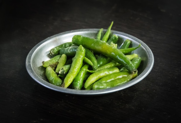 Piments verts marinés dans un bol métallique sur fond noir. piment