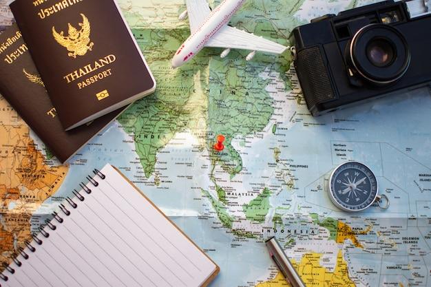 Pin sur la carte de localisation pour plan de voyage avec caméra boussole passeport et un cahier.