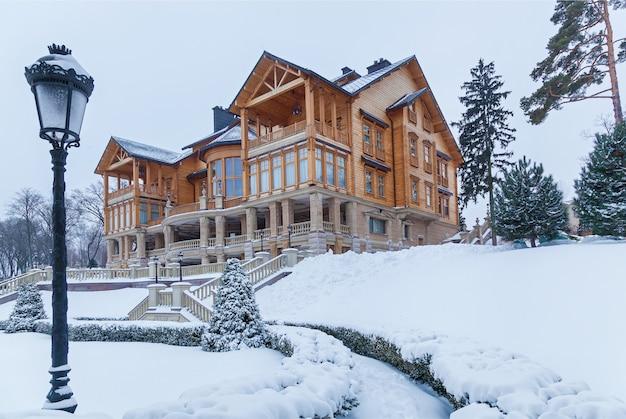 Le pin est recouvert de neige près de la maison à mezhyhiria. pin dans la neige près de la maison.