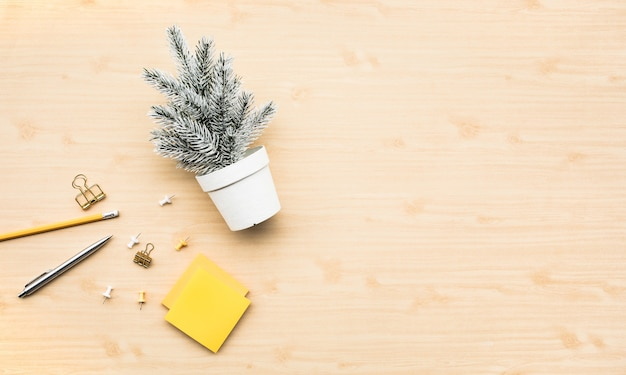 Pin mignon maquette en pot blanc et accessoires stationnaires sur fond de table de travail en bois.joyeux noël et hiver concepts idées.style minimal