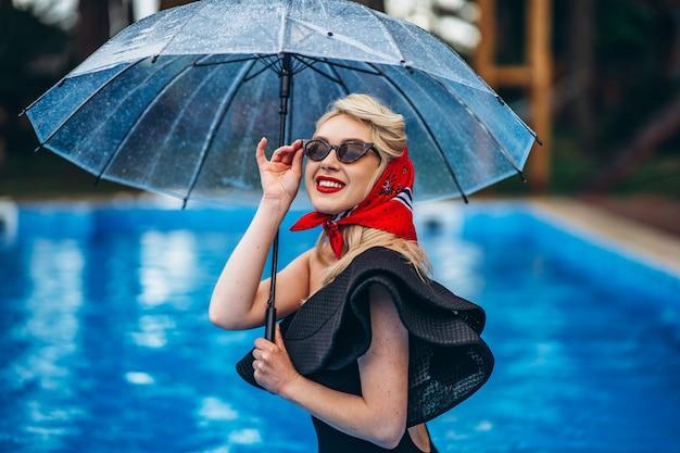 Pin up blonde de style avec des lunettes de soleil avec parapluie et amusez-vous dans la piscine