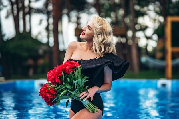 Pin up blonde de style en maillot de bain vintage noir se détendre dans la piscine en plein air