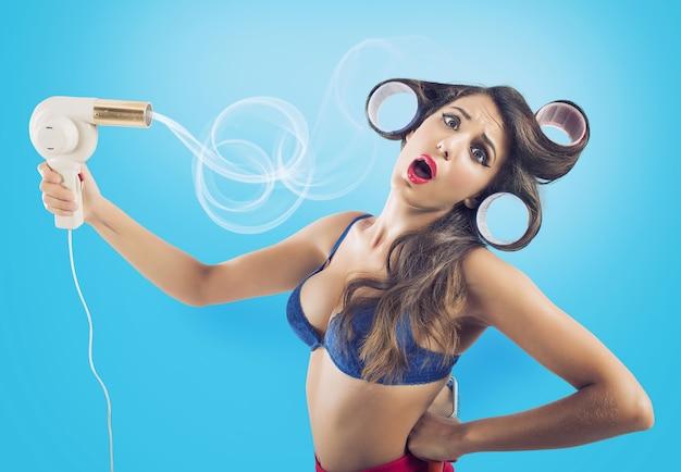 Une pin-up brune sèche ses cheveux longs avec un sèche-cheveux