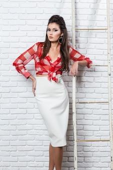 Pin up comme style portrait d'une belle jeune brune sur un mur de briques blanches