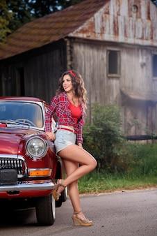 Pin-up femme posant près d'une voiture vintage rouge à la campagne.