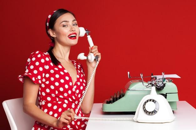 Pin up girl tapant sur une machine à écrire