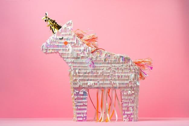Pinata licorne pour fête d'enfants sur fond rose se bouchent