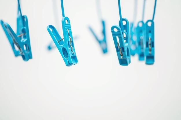 Pince à linge closeup bleu sur fond texturé ciment blanc flou