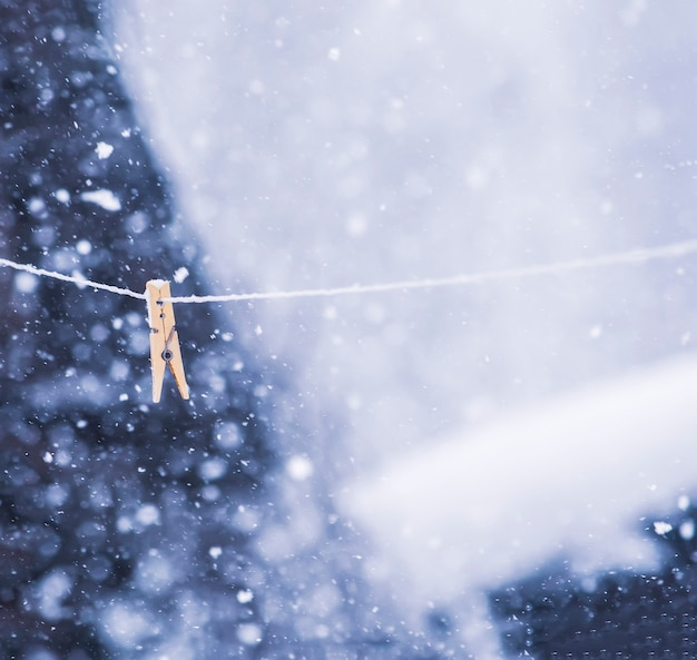 Pince à linge colorée sur la corde dans une tempête de neige à l'extérieur