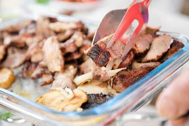 Pince avec morceau de viande grillée et oignons