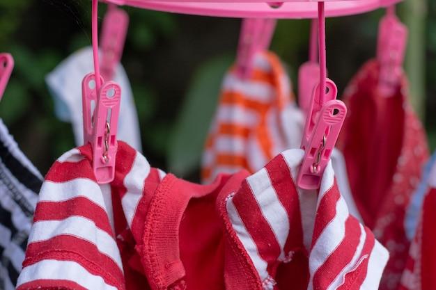 Pince en plastique rose pour le serrage des vêtements.