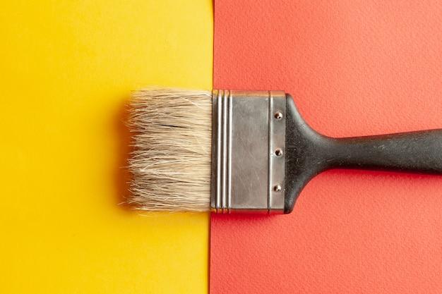Un pinceau à l'arrière-plan de papier jaune et rouge