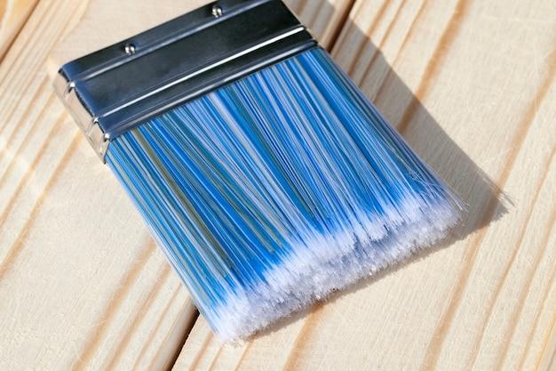 Pinceau en bois à poils bleus pour peindre un parquet en pin