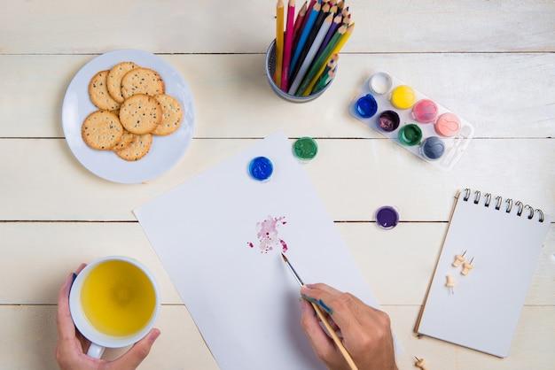 Pinceau, carnet de croquis et couleurs à l'aquarelle sur table.