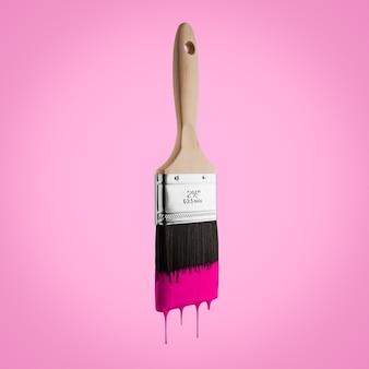 Pinceau chargé de couleur rose dégoulinant des soies - isolé sur fond rose.