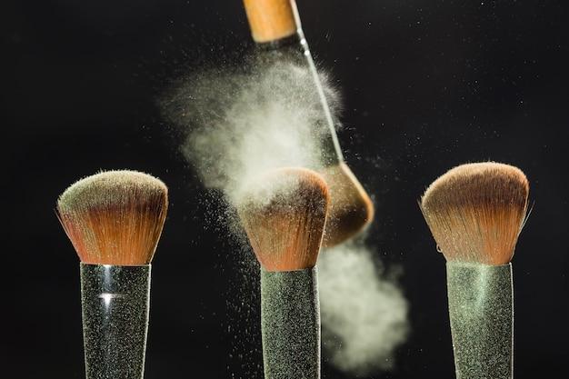 Pinceau de concept de maquillage et de cosmétiques minéral brossant la poudre blanche d'un autre sur le noir