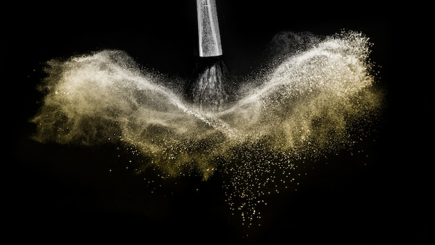 Pinceau cosmétique avec épandage de poudre cosmétique dorée