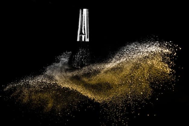 Pinceau cosmétique avec poudre cosmétique dorée se répandant pour maquilleuse et graphisme sur fond noir