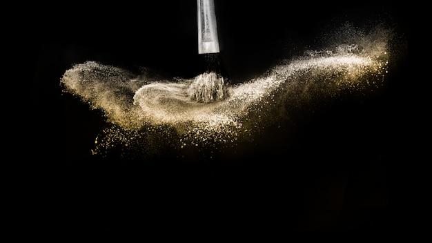 Pinceau cosmétique avec poudre cosmétique dorée se répandant pour maquilleuse