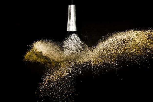 Pinceau cosmétique avec poudre cosmétique dorée