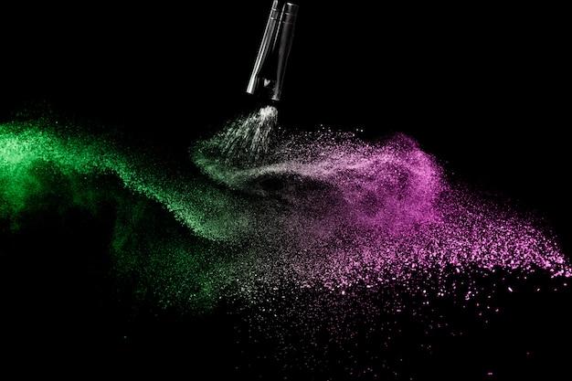 Pinceau cosmétique avec poudre cosmétique verte et rose se répandant pour maquilleuse et graphisme sur fond noir