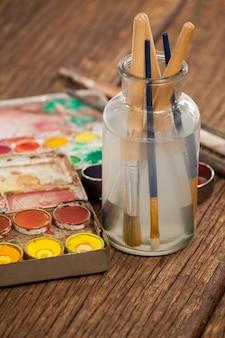 Pinceau dans un pot rempli d'eau et d'aquarelles sur table en bois