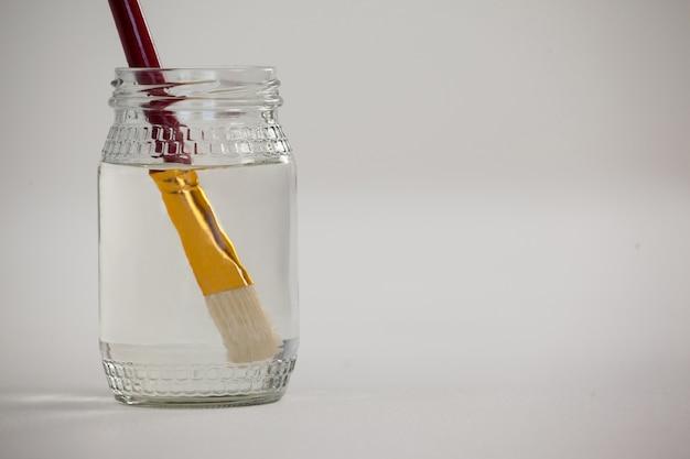 Pinceau Dans Un Pot Rempli D'eau Contre Une Surface Blanche Photo Premium