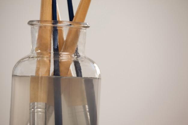 Pinceau dans un pot rempli d'eau contre une surface blanche