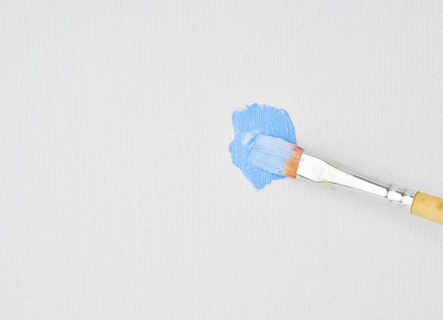 Pinceau dessine la peinture bleue sur la toile, en gros plan. action peinture art. l'artiste a commencé à peindre