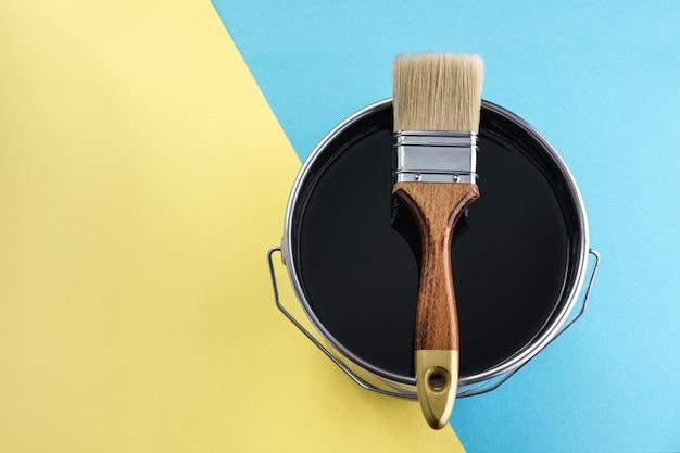 Pinceau sur le dessus de la boîte de peinture de couleur noire sur fond jaune et bleu avec espace de copie