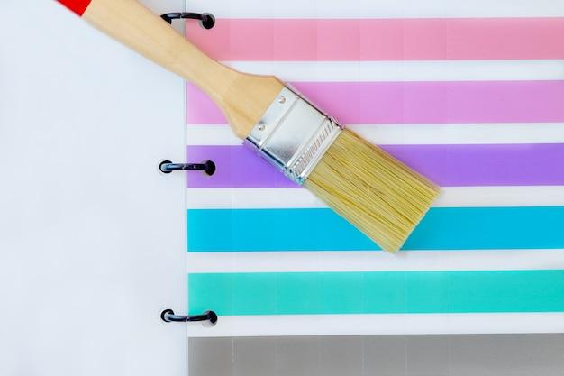 Pinceau et échantillons de peinture colorée sur fond blanc avec espace de copie.