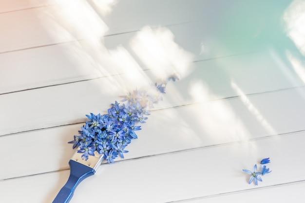 Pinceau fait de fleurs bleues sur une table en bois blanche