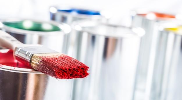Pinceau gros plan de couleur rouge posé sur un pot de peinture.