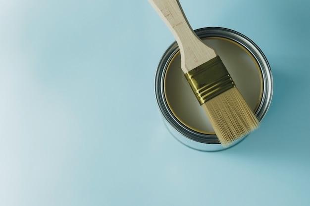 Pinceau avec manche en bois et boîte de peinture blanche ouverte sur fond bleu cyan