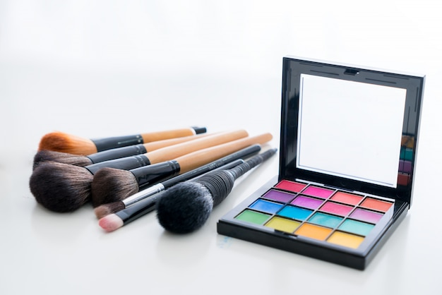 Pinceau de maquillage divers avec des produits de maquillage et cosmétiques anticernes sur table en fond blanc.
