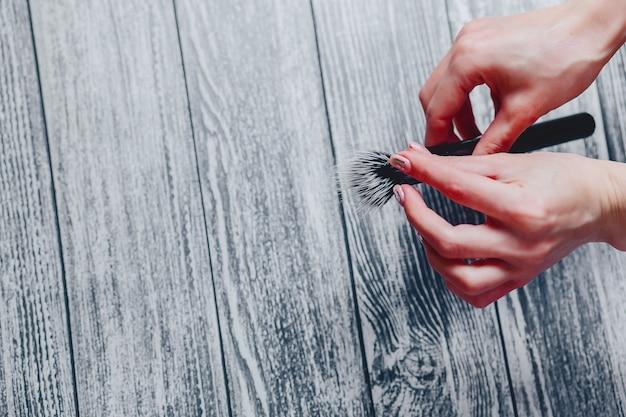 Pinceau de maquillage en mains sur fond en bois