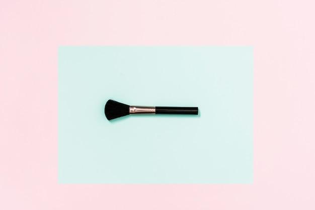 Pinceau de maquillage noir sur fond bleu sarcelle et rose