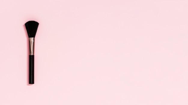 Pinceau de maquillage noir sur fond rose
