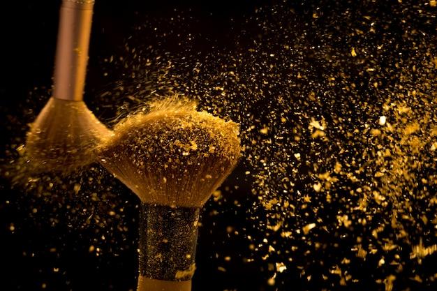 Pinceau de maquillage avec poudre cosmétique dorée se répandant sur fond noir